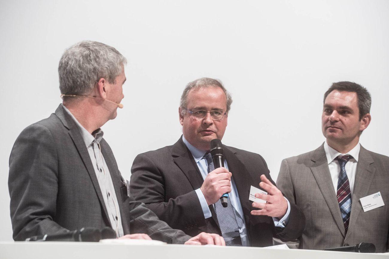 Der Moderator und zwei Herren am Rednertisch