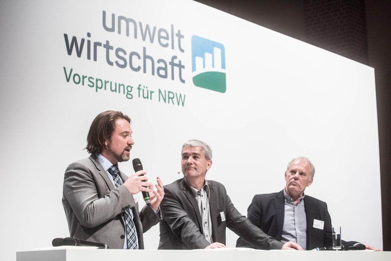 Drei Herren am Rednertisch, links Herr Stiebel mit Mikrophon
