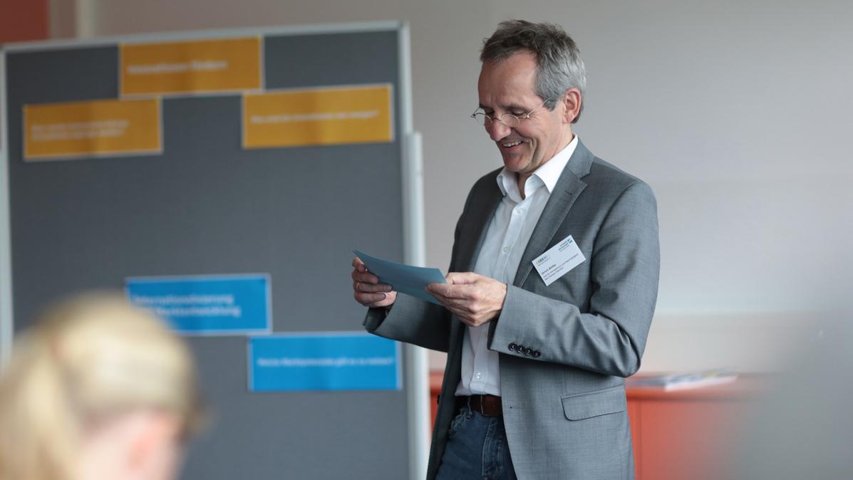 Ulrich Ahlke steht vor dem Präsentationsboard und schaut auf seine Karteikarten.