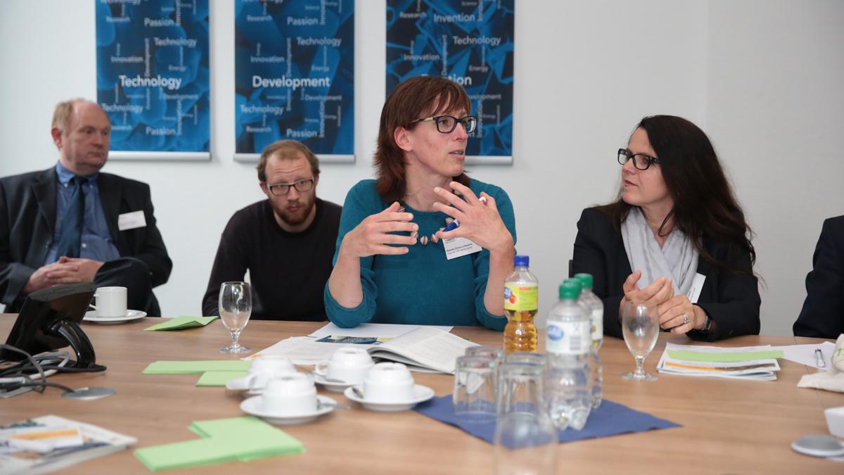 Zwei Frauen und zwei Männer sitzen am Tisch und diskutieren angeregt.