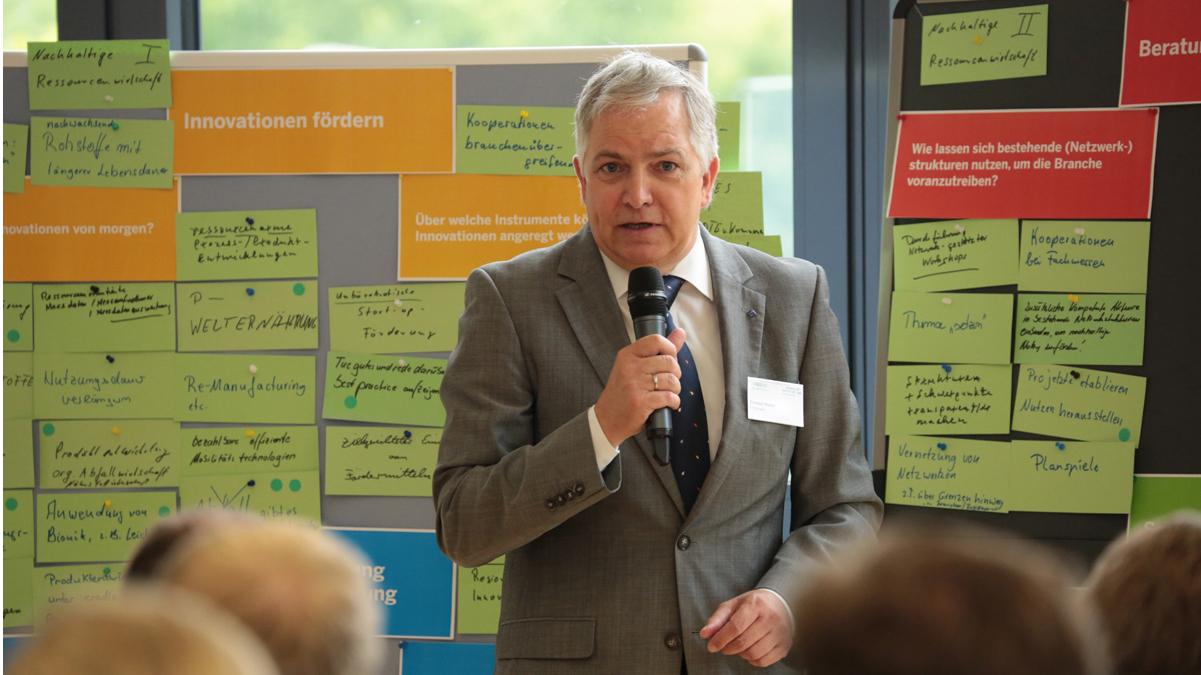 Prof. Dr. Christoph Wetter (FH Münster) steht vor der Projekttafel und hält einen Vortrag.