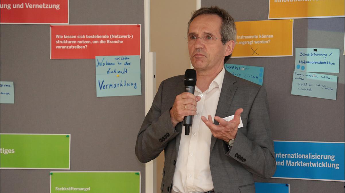 Ulrich Ahlke steht vor der Präsentationswand und spricht ins Mikrofon.