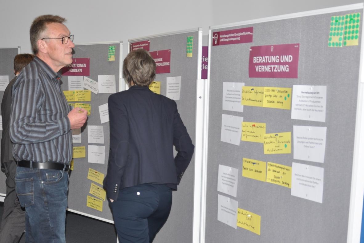 Konferenzteilnehmer begutachtet aufmerksam die Plakatwand.
