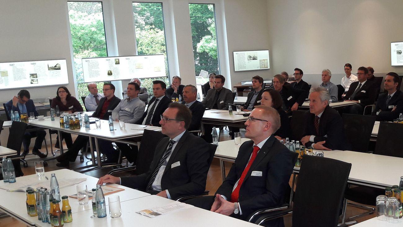Teilnehmerinnen und Teilnehmer an Konferenztischen