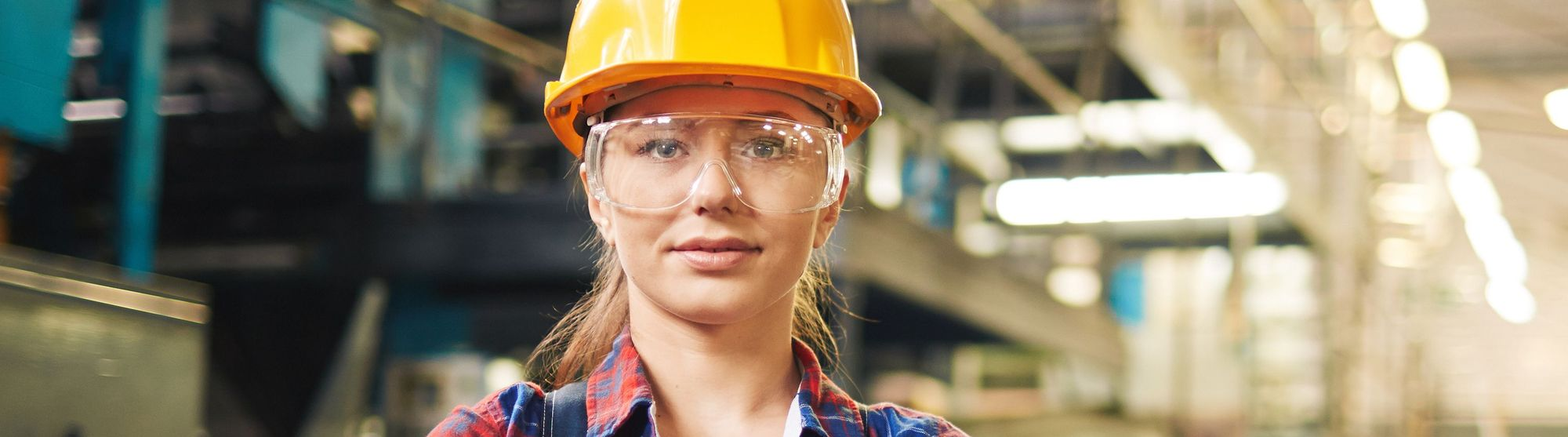 Eine Frau mit Bauhelm und Schutzbrille in einer Fabrikhalle