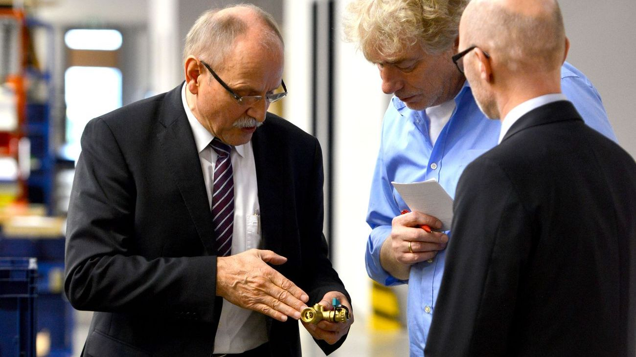 Drei Herren in einer Werkshalle betrachten eine Kupferarmatur