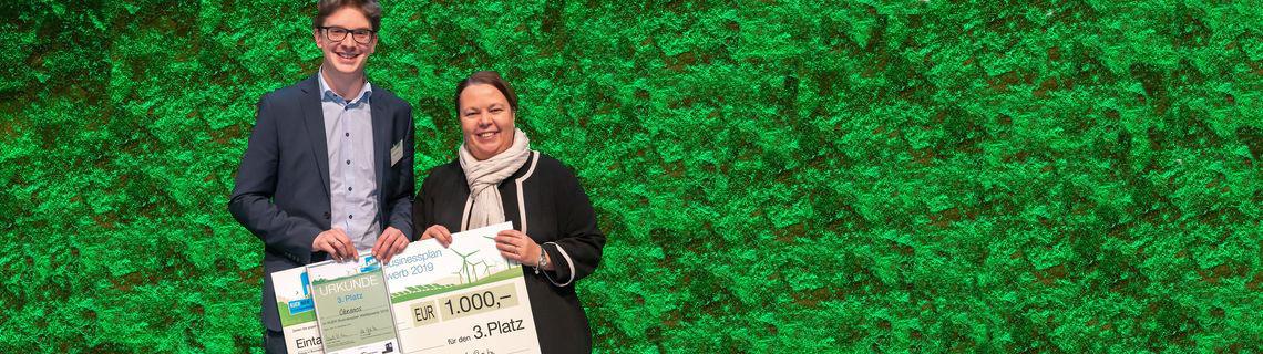 Die Ministerin überreicht einen großen Scheck an den Gewinner des KUER-Wettbewerbs