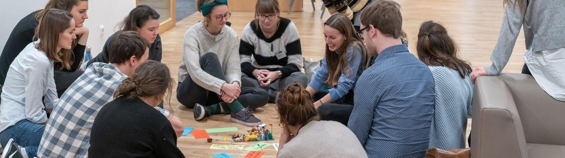 Studentinnen und Studenten in einem Sitzkreis diskutieren